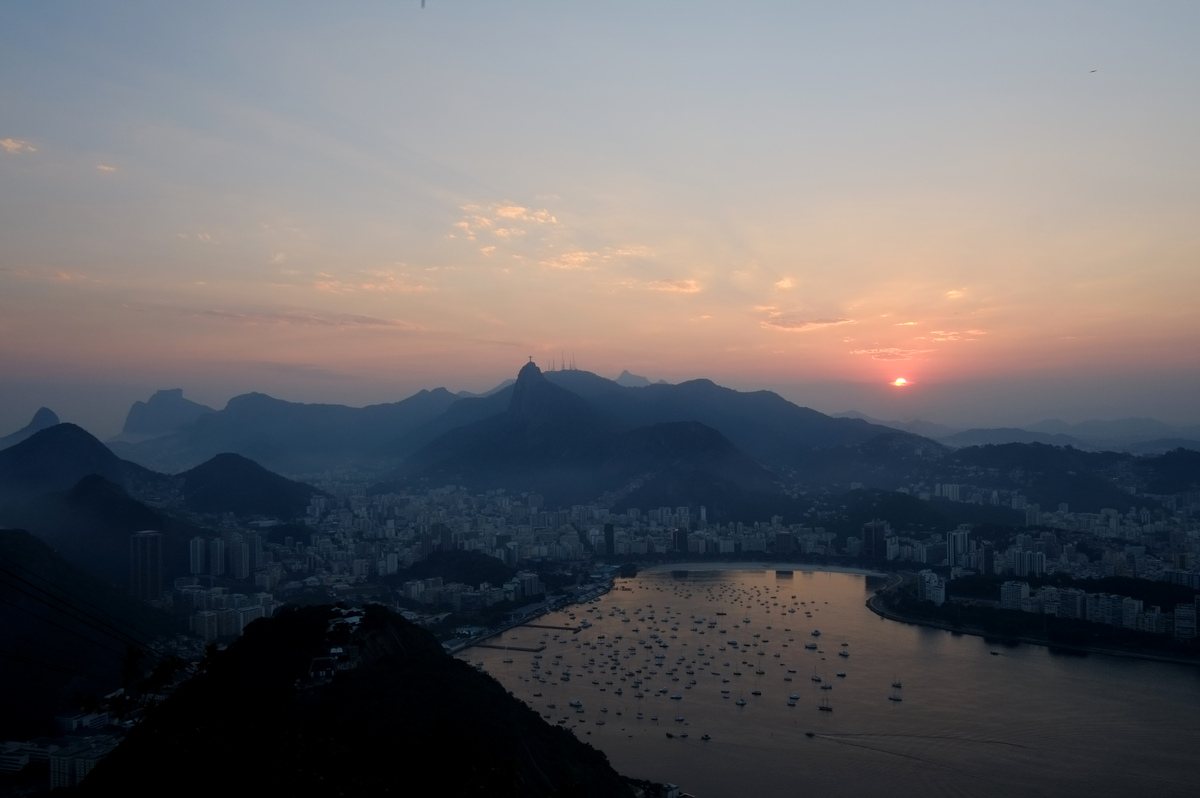The sun sets on Botafogo bay with the Christ the Reedemer statue on the Corcovado mountain in the background in Rio de Janeir