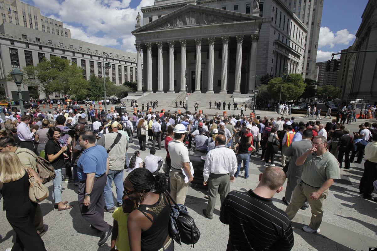 People stand in Foley Square in New York after being evacuated from the Federal and State buildings that surround it Tuesday,