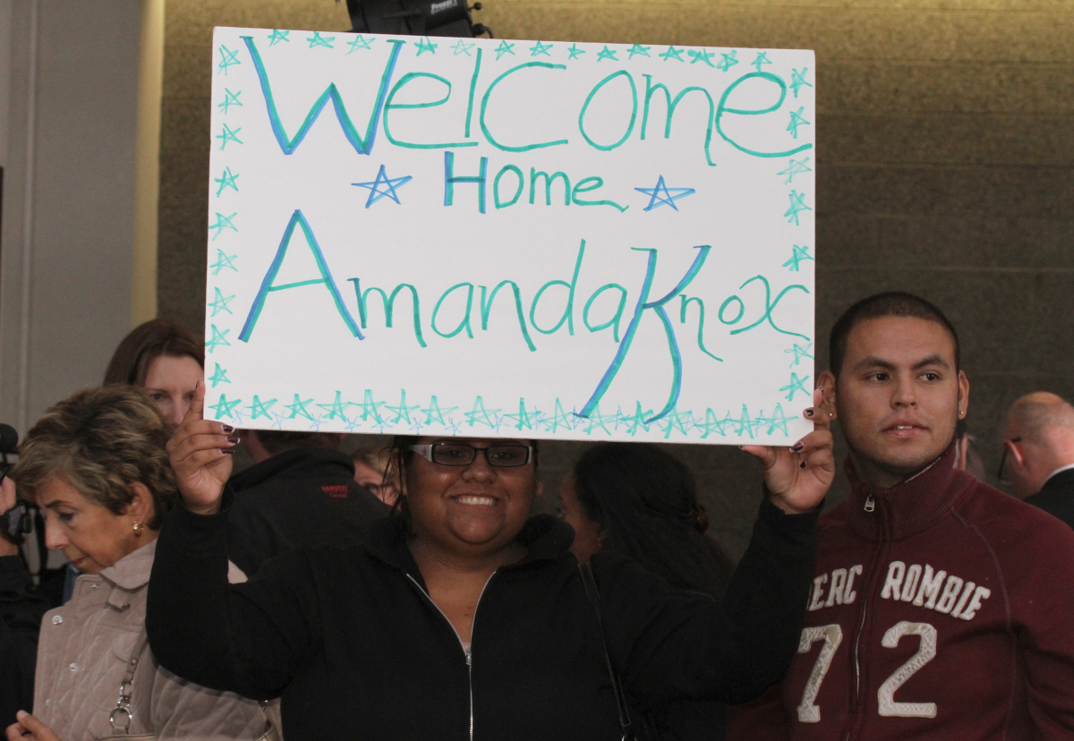 A supporter for Amanda Knox holds a sign at a news conference shortly after her arrival at Seattle-Tacoma International Airpo