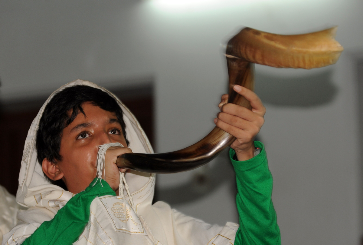 A Jewish Indian boy blows the shofar to gather devotees around the Torah at the Magen Abraham Synagogue in Ahmedabad on Sept.