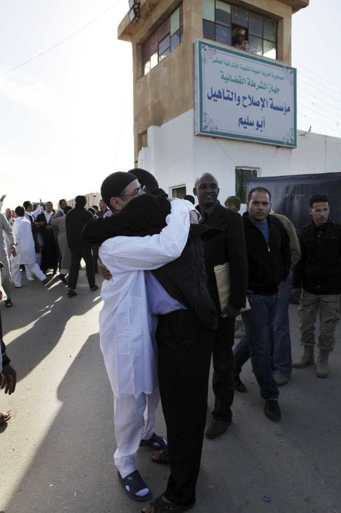A Libyan prisoner, left, is hugged by his relatives after he was released with a group of 110 prisoners from Abu Salim, Libya