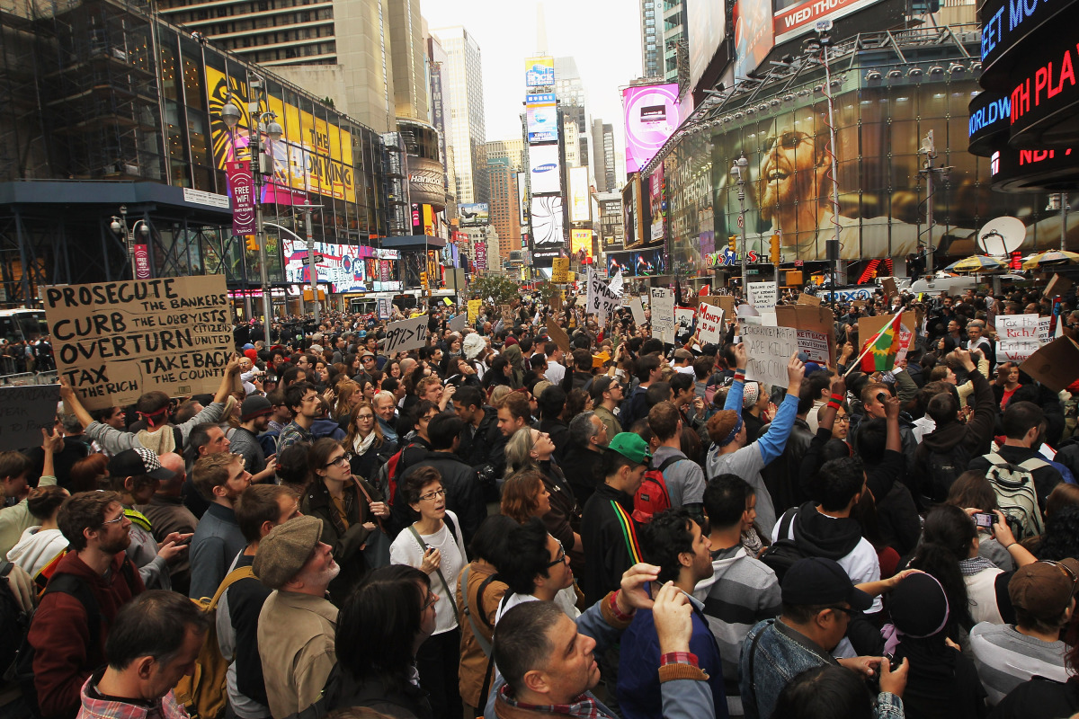 NEW YORK, NY - OCTOBER 15:  Demonstrators associated with the 'Occupy Wall Street' movement protest in Times Square on Octobe