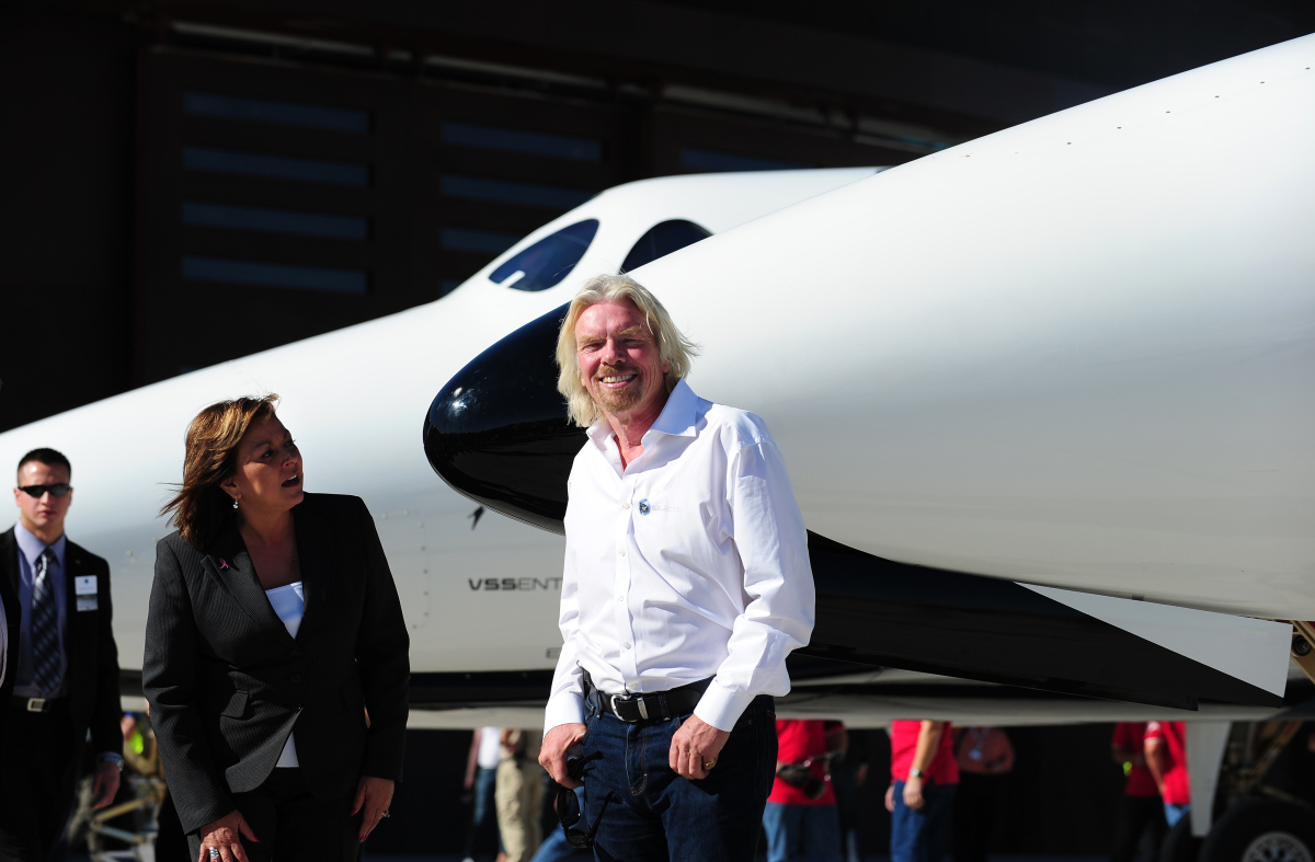 Sir Richard Branson and New Mexico Governor Susana Martinez are seen in front of WhiteKnightTwo, which carries SpaceShipTwo,