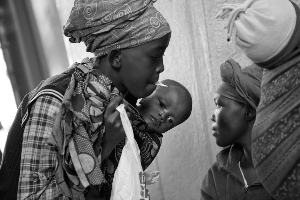 A young mother with her child waits her turn, with ticket in mouth, to be seen by the clinic nutritionist. The clinic has ove