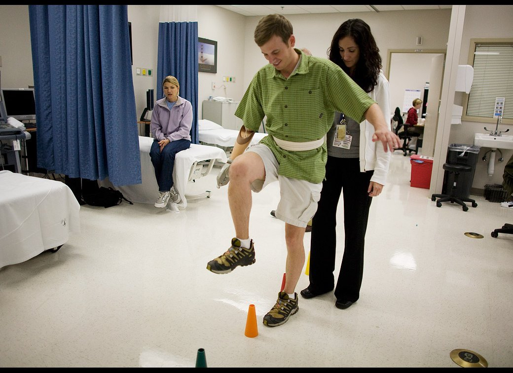 Physical therapist Kyla Dunlavey works with Sgt. Ted Wade of the 82nd Airborne while his spouse Sarah Wade watches at Walter