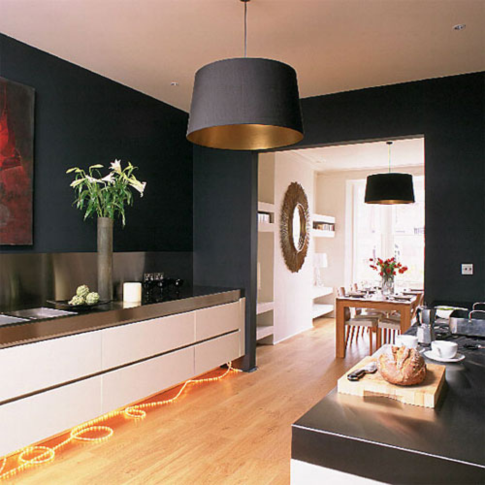 The black walls make this kitchen look modern and sophisticated, and we love how it contrasts with the dining room.   Flick