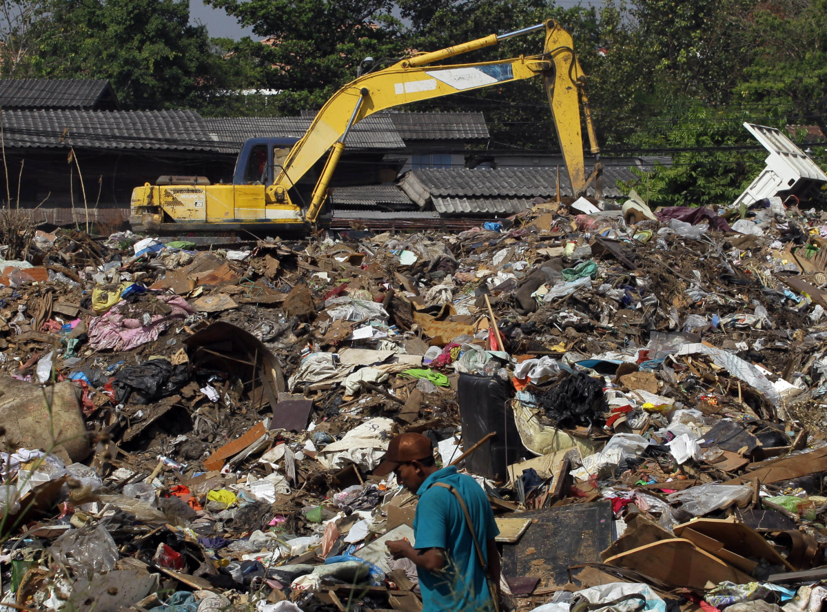A man sifts through pile of garbage, left over after the flood, at a temporary dump site on the outskirts of Bangkok, Thailan