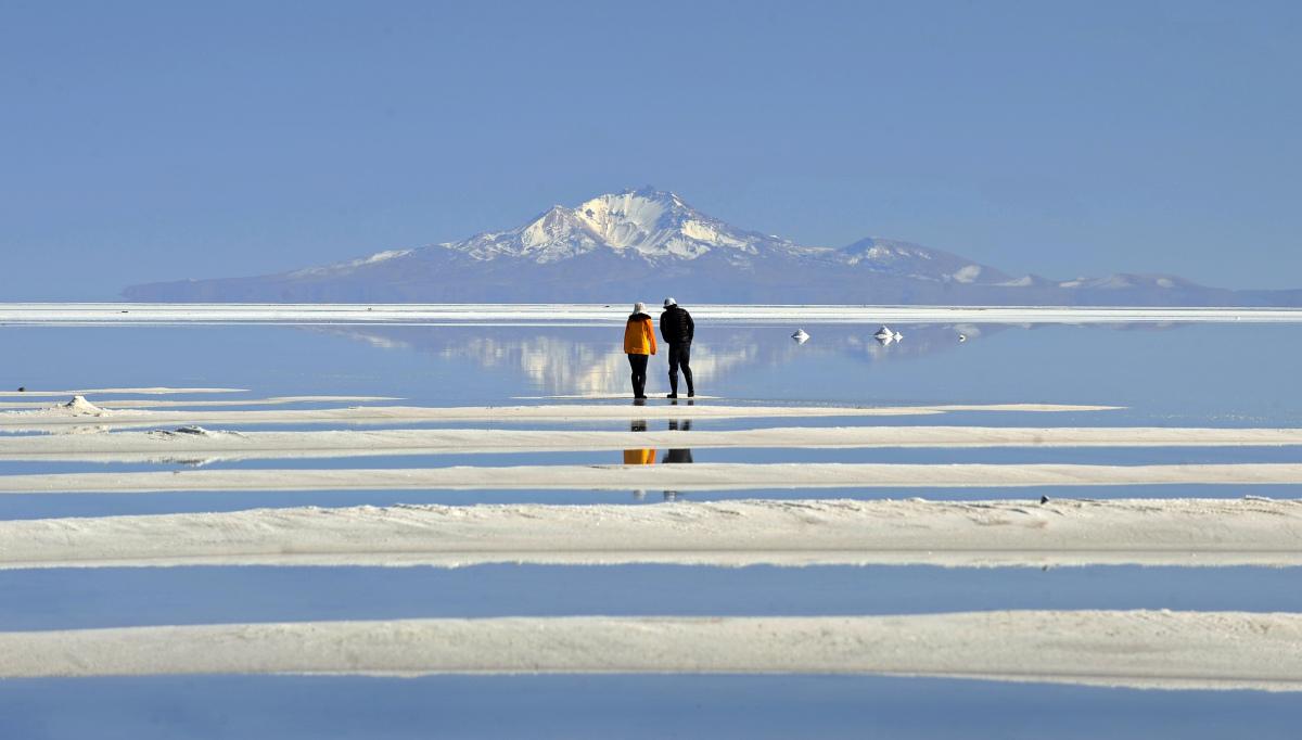 A Japanese tourist couple walks in the world's largest salt flat of Uyuni, 550 Km southwest of La Paz, Bolivia on July 20, 20