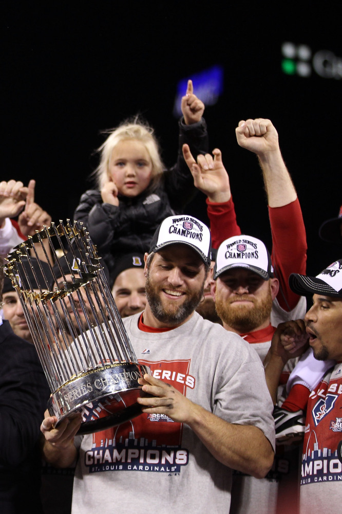Lance Berkman #12 of the St. Louis Cardinals celebrates with the World Series trophy after defeating the Texas Rangers 6-2 in