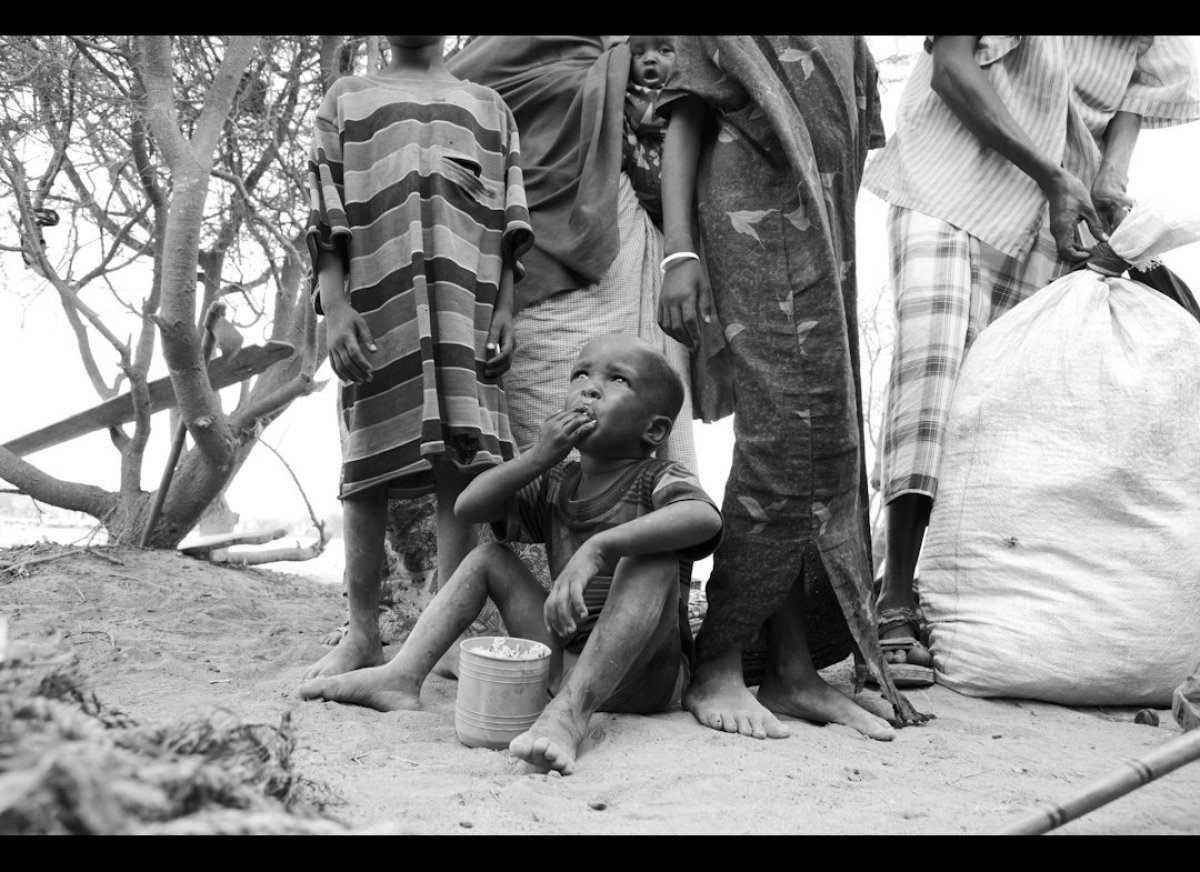 A child eats a meager portion of rice that is his ration of food for the day. His family has been living and sleeping outside