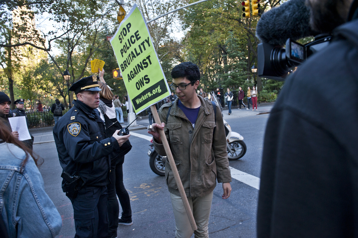 Student Cameron Shahraray is warned by police during an 'Occupy Wall Street' march. Universities from around New York joined