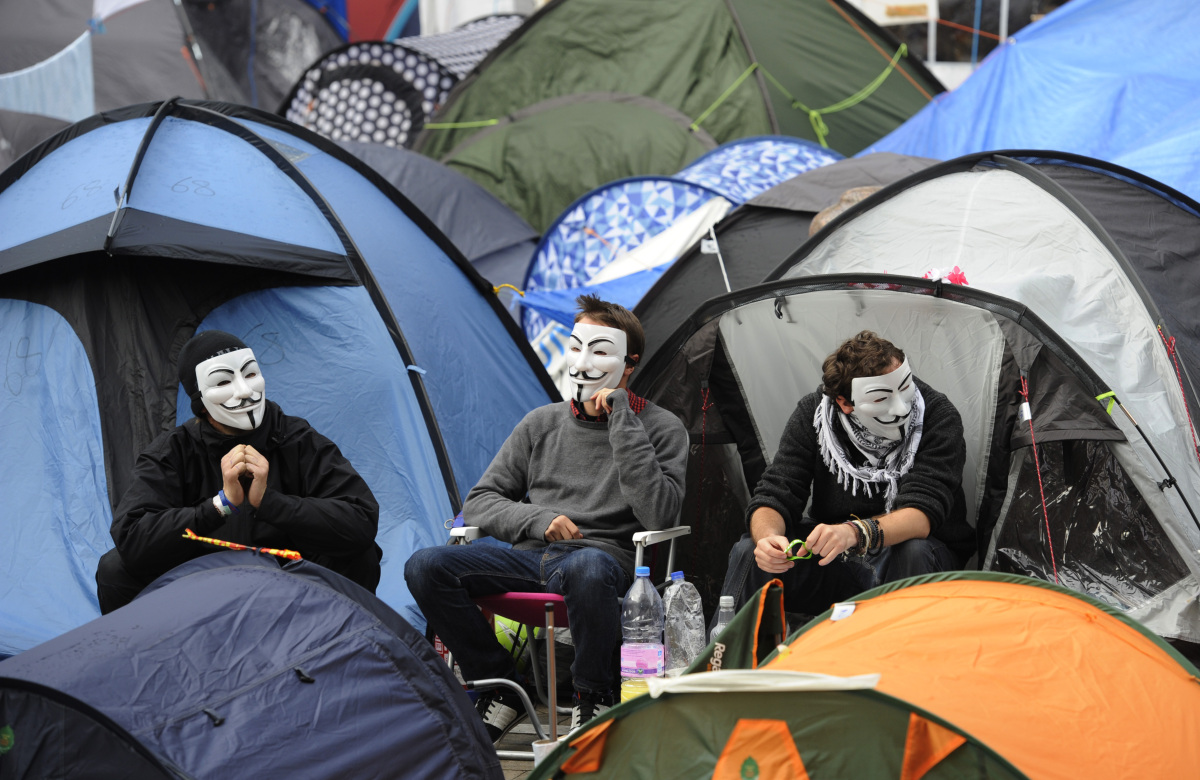 Demonstrators wearing V for Vendetta masks sit outside tents at the Occupy London camp outside St. Paul's Cathedral in London