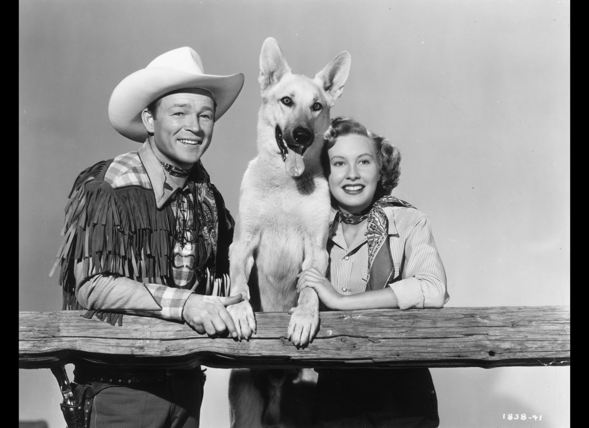 circa 1951: American cowboy actor Roy Rogers (1911 - 1998) stands next to his costar, actor Penny Edwards, and a German sheph