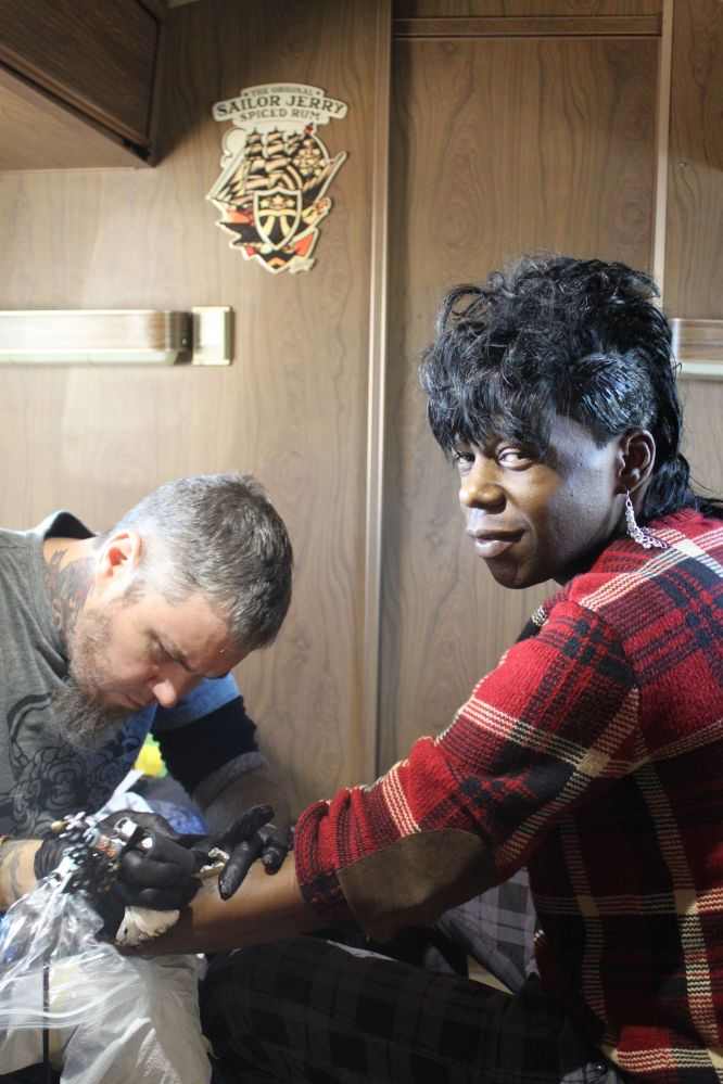 """Big Freedia poses in the Sailor Jerry trailer onsite at Fun Fun while getting a tattoo of a pin-up girl with the words """"Azz E"""