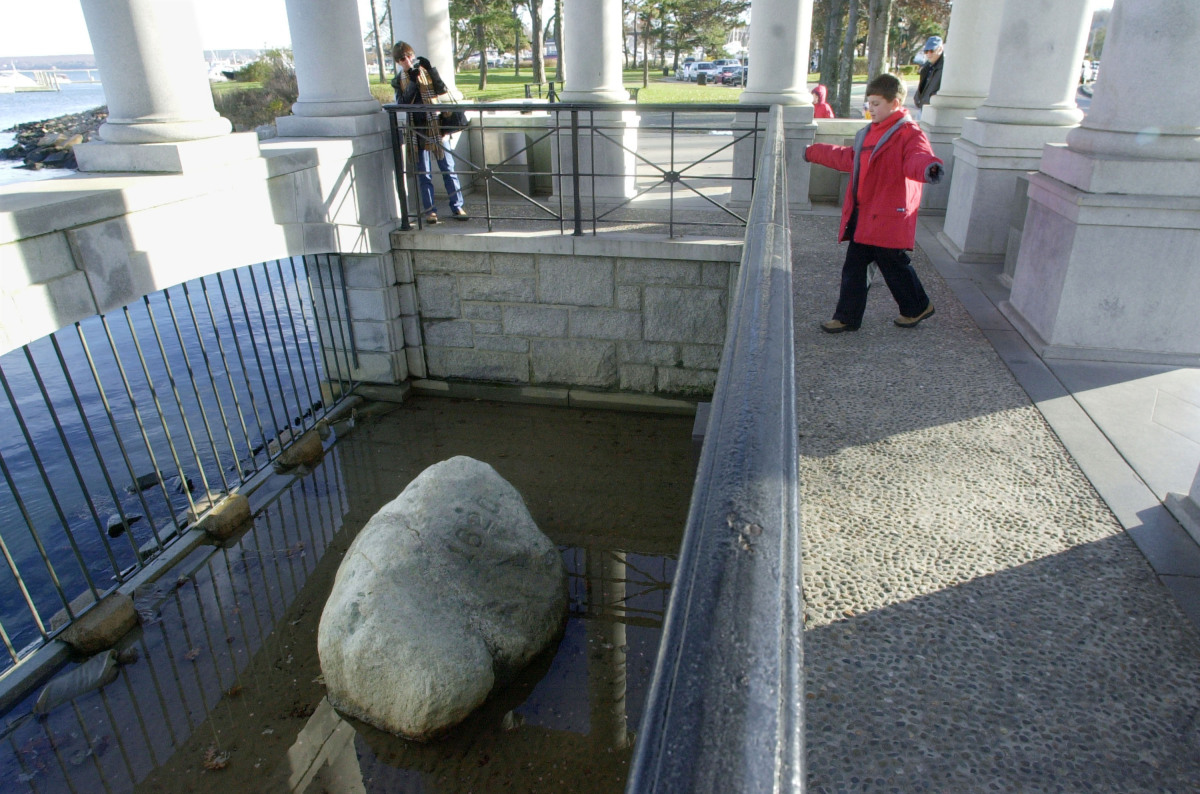 Visitors look over a railing at Plymouth Rock, which according to tradition marks the spot where the pilgrims first came asho