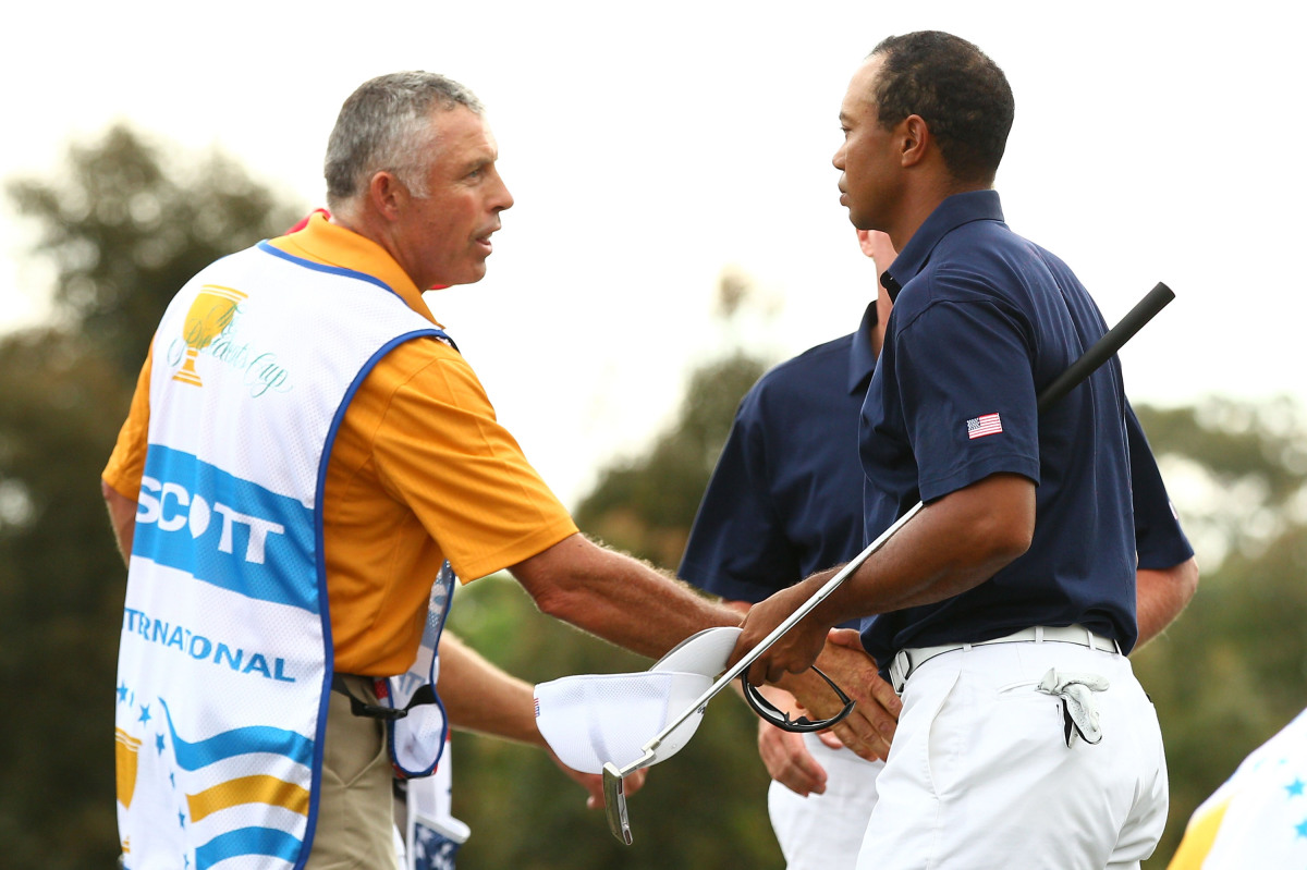 Tiger Woods of the U.S. Team and Steve Williams, caddie to Adam Scott (not pictured), shake hands after the completion of the