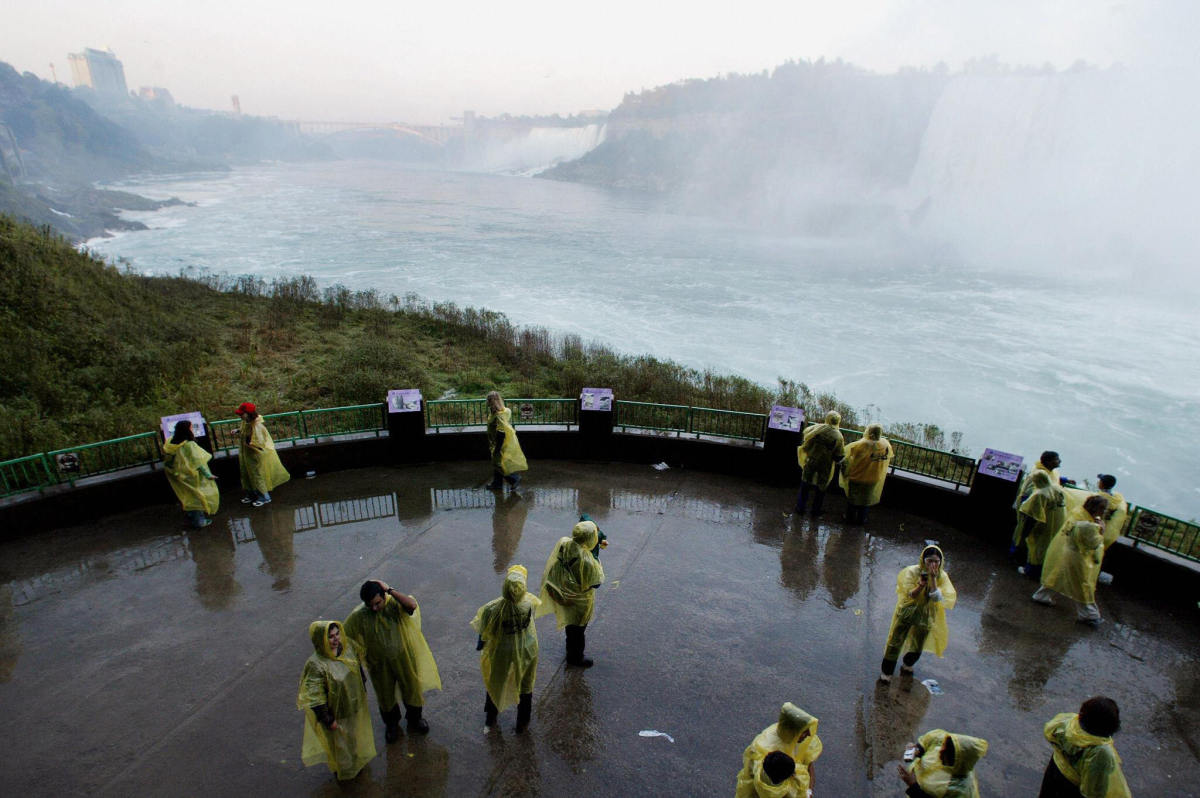 <em>Tourists are sprayed with mist as they enjoy the view near the bottom of Niagara Falls, 10 October 2003. Thousands of tou