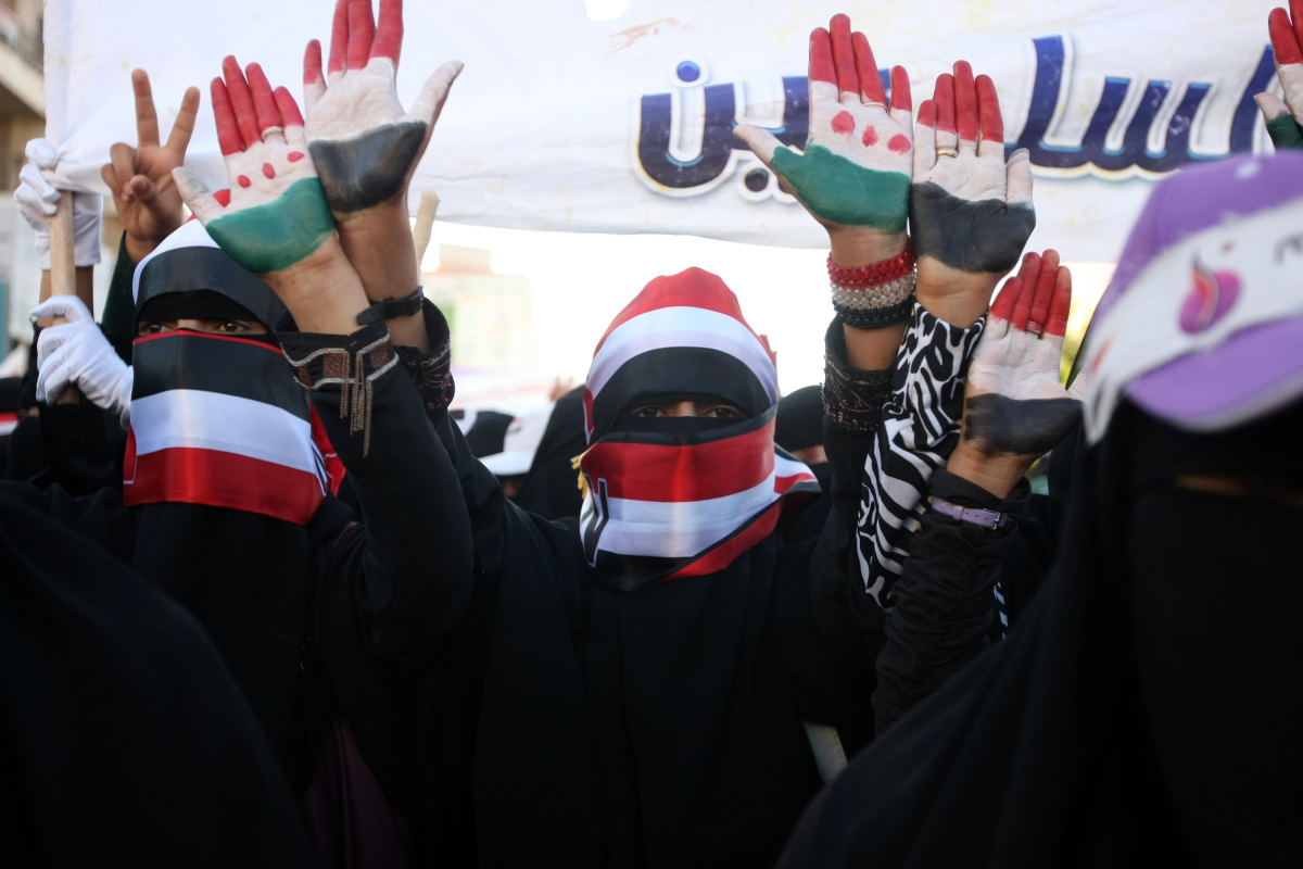 Photo: Yemeni anti-regime protesters covering their faces with the Yemeni flag take part in a protest in Sanaa on November 14