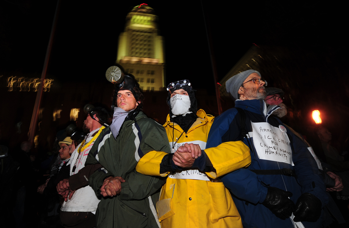 Anti-Wall Street demonstrators wearing gas masks lock arms to hold their position just before midnite on Nov. 29, 2011 in Los