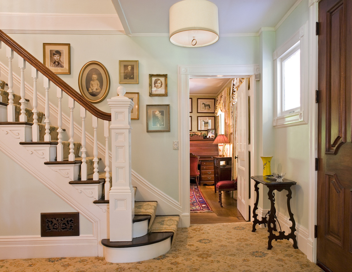 Hang photos in an ascending style along the staircase to add a personal touch to the entryway. It will provide an inviting at