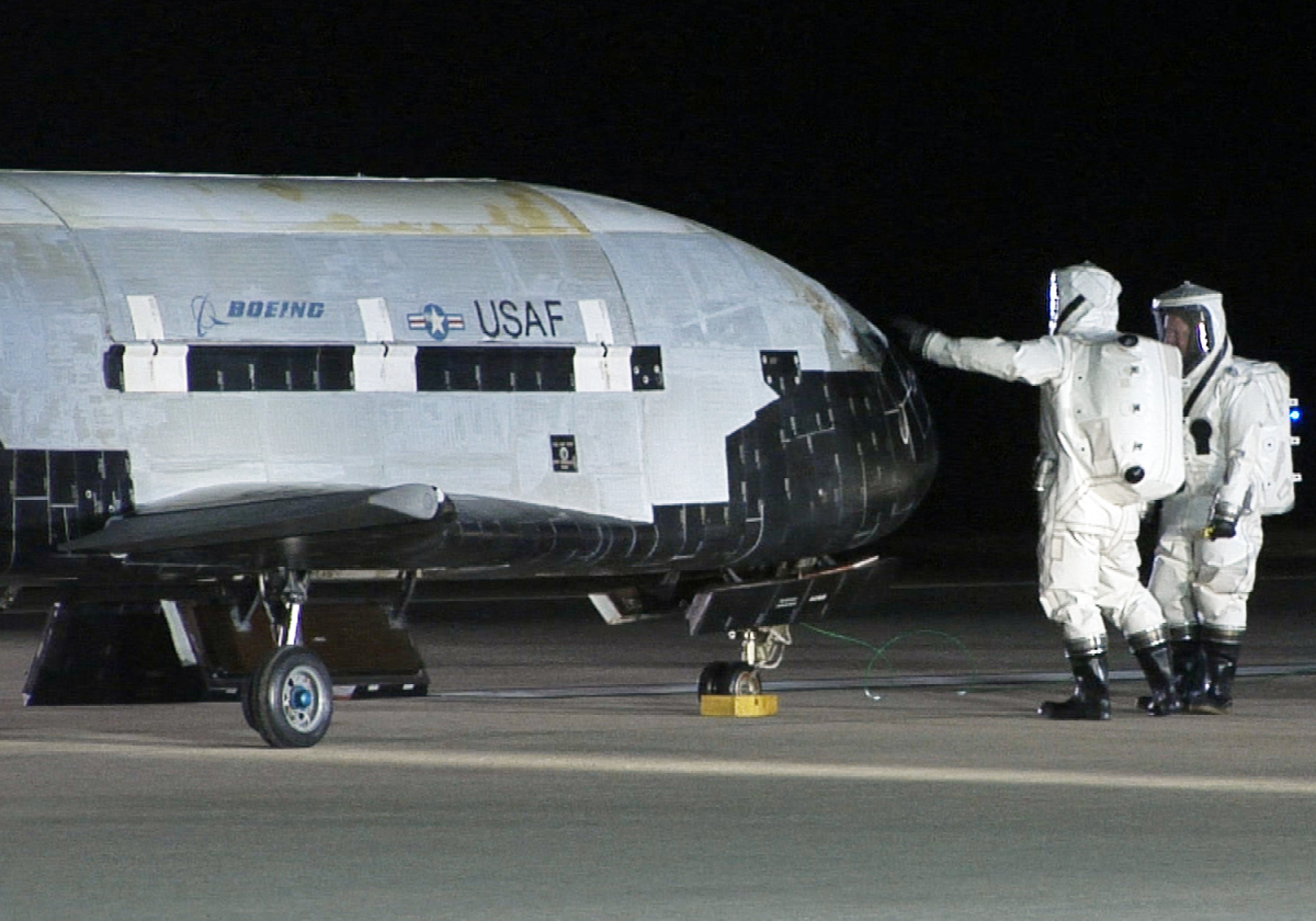 This picture provided by the US Air Force shows personnel inspecting the X-37B, the Air Force's first unmanned re-entry space