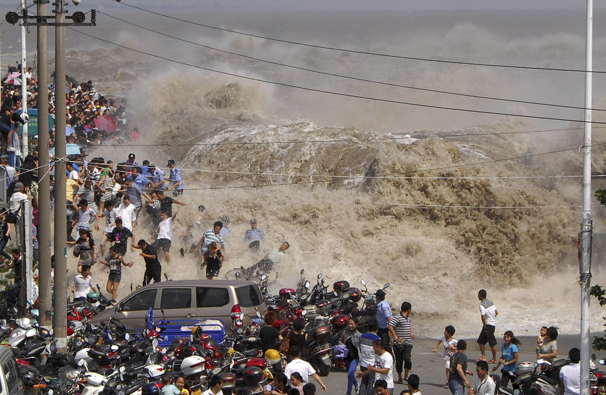 In this Wednesday Aug. 31, 2011 photo, spectators flee as waves created by a tidal bore crash over a barrier on the Qiantang