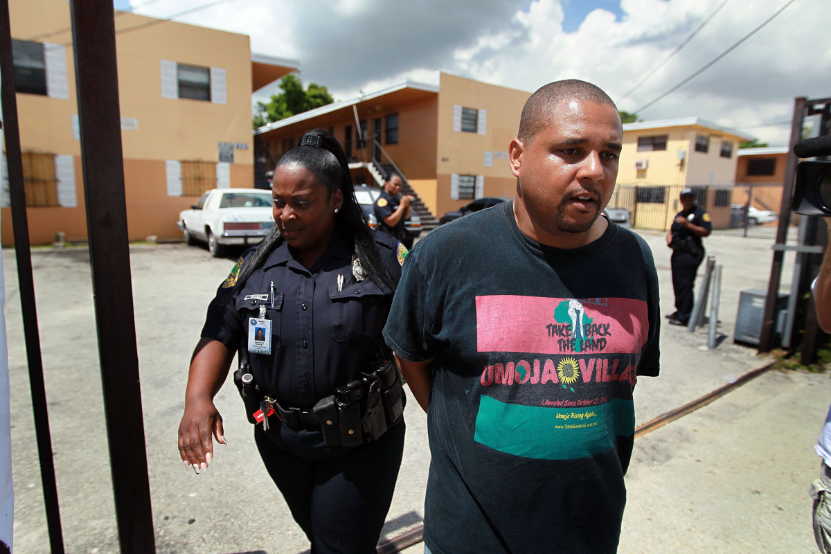 Max Rameau is led away by a City of Miami police officer when he was arrested during a protest against the evictions being ca