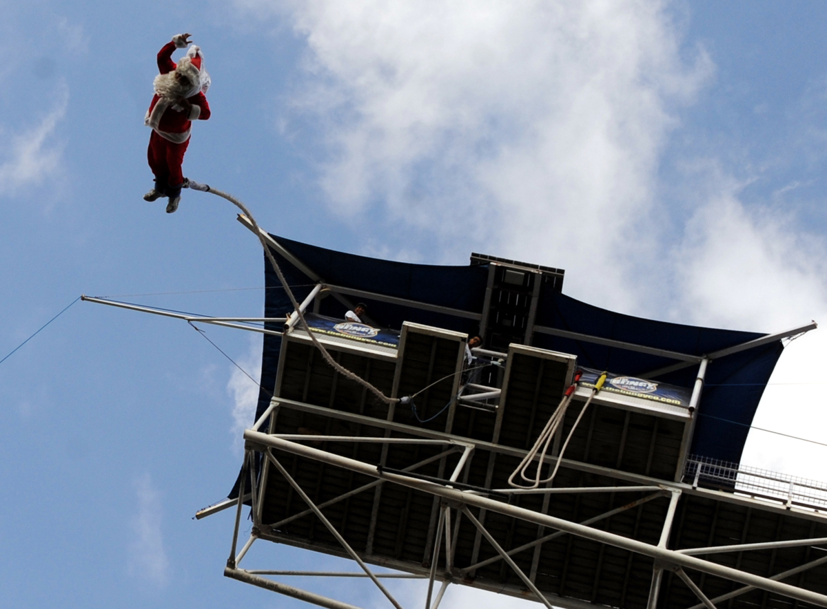 A bungee jumper dressed as Santa Claus leaps from a platform above Kuta beach in Denpasar on Indonesia's resort island of Bal