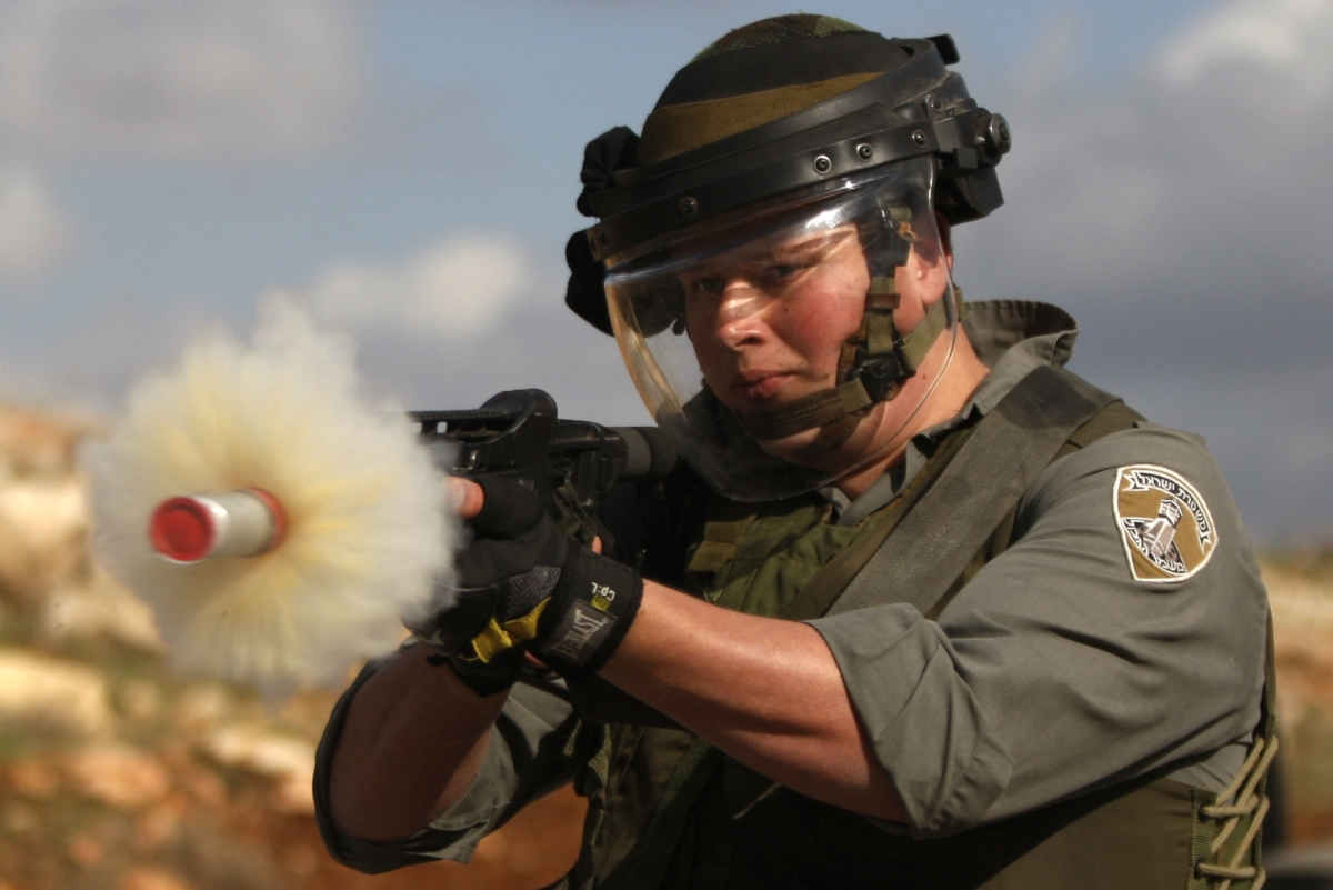 An Israeli border policeman fires tear gas at Palestinian protesters during a demonstration against the expansion of the near
