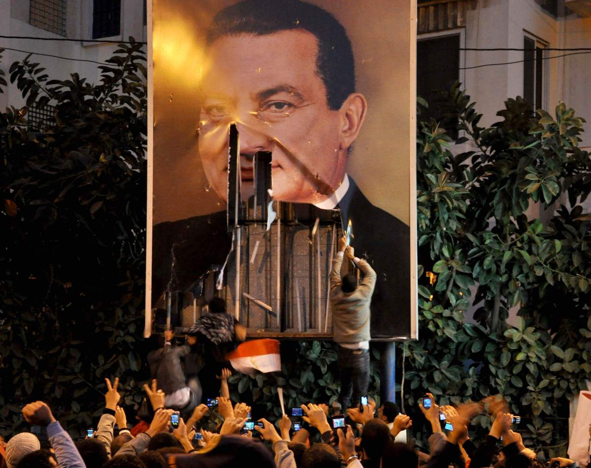 Demonstrators deface a poster of  Egyptian President Hosni Mubarak in Alexandria, Egypt, Tuesday, Jan. 25, 2011. Thousands of