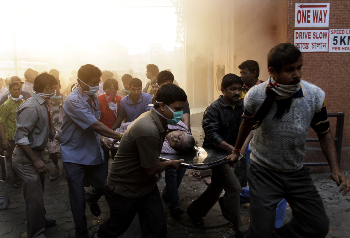 People evacuate patients after a fire broke out at a nursing home in Kolkata, India, on Dec. 9, 2011. The fire swept through