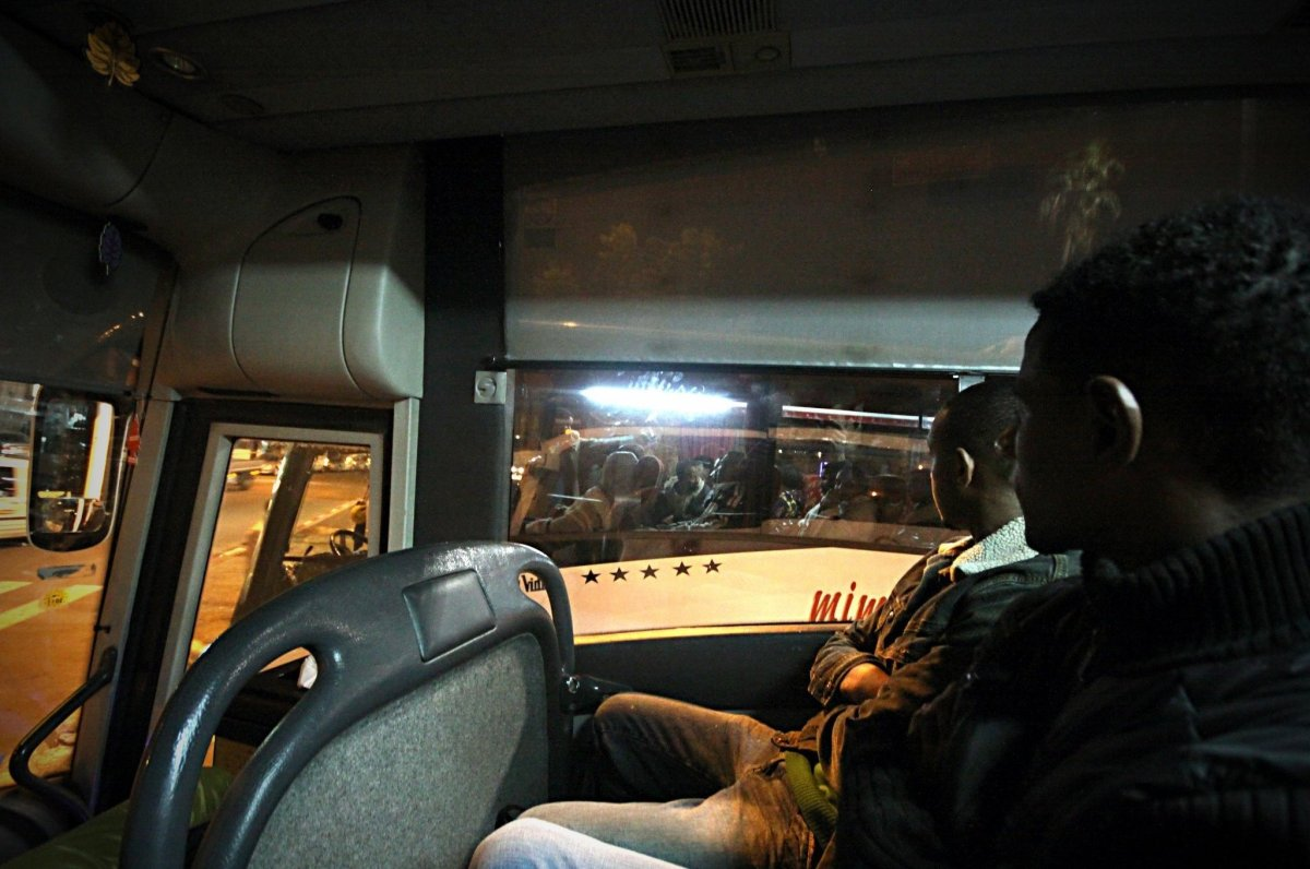 Two brothers from Eritrea, 26 and 23, watch a bus of African refugees passes by on the way to Bethlehem for the Coptic Christ