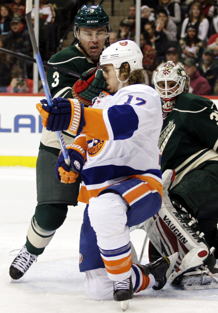 New York Islanders winger Matt Martin (17) takes a glove to the face as he is defended by Minnesota Wild defenseman Marek Zid