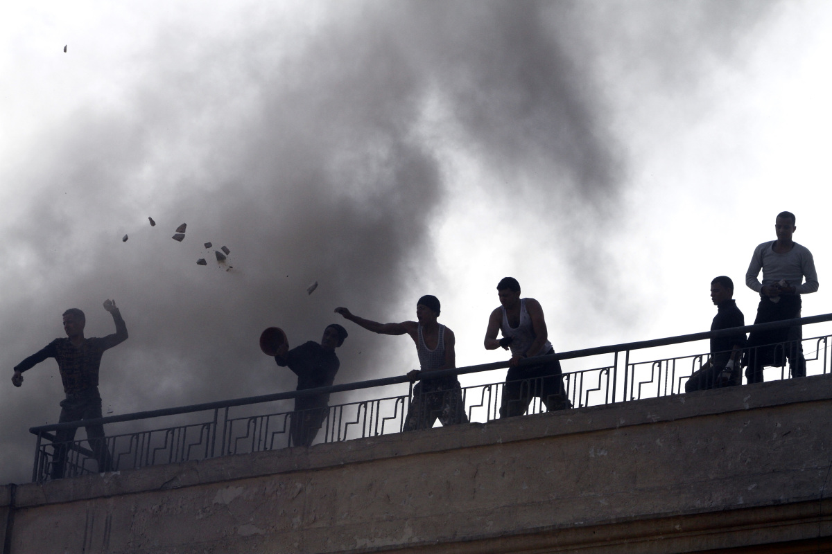 Supporters of the military rulers of Egypt throw stones at opponents demonstrating against the army rule from the roof of the