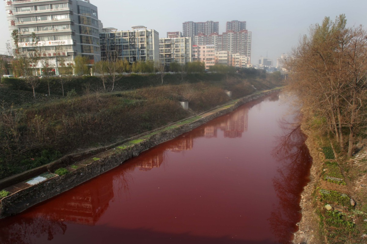 This picture taken on Dec. 13, 2011 shows the red polluted Jian River in Luoyang, north China's Henan province. The cause of