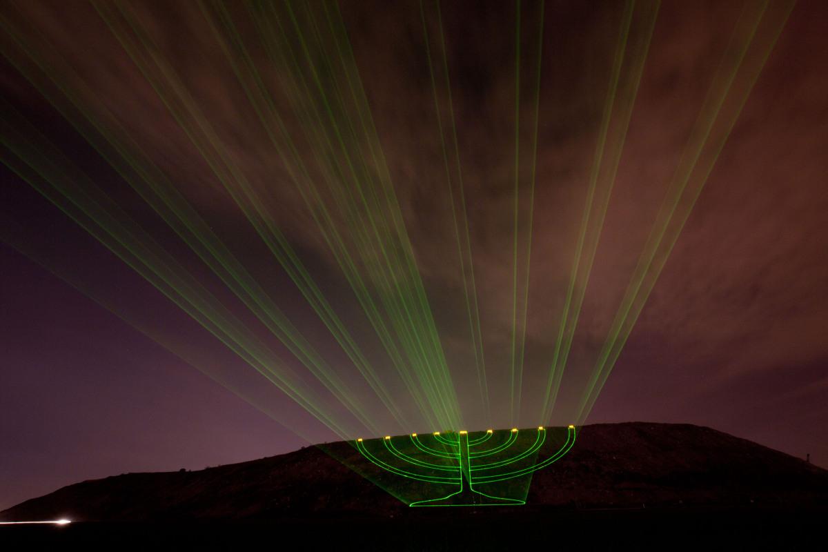 Laser beams creating the image of a large lit Hanukkah menorah are projected on the Hiriya landfill, a former waste disposal