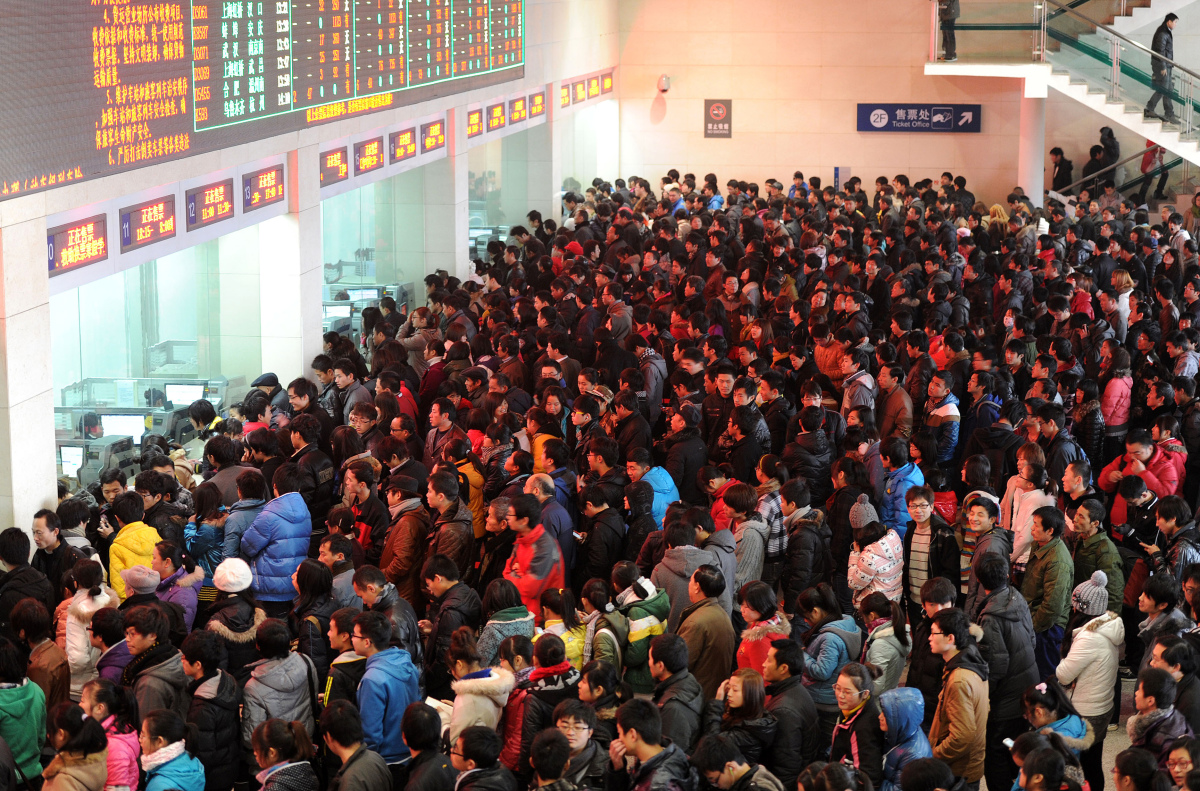 Hundreds of Chinese people queue up to buy train tickets at a railway station in Hefei, east China's Anhui province.