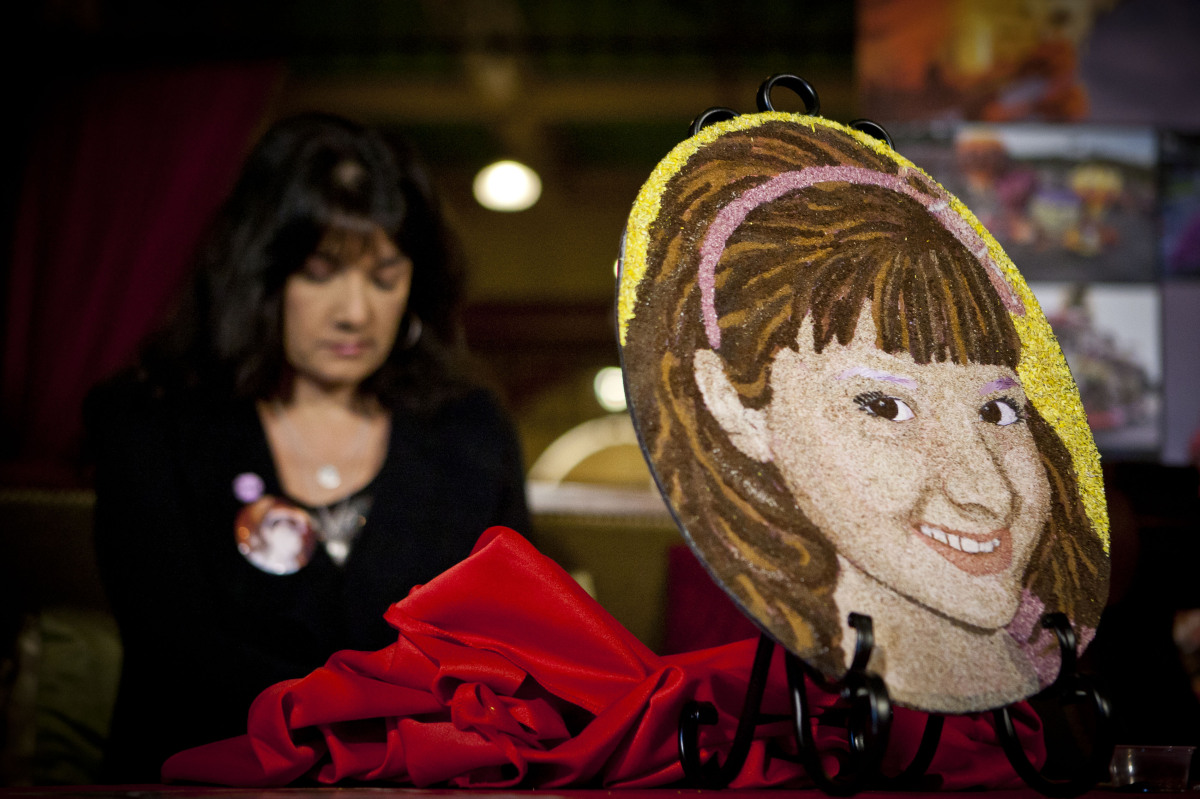 Roxanna Green, sits behind a floral portrait of her daughter Taylor, Saturday, Dec. 31, 2011, at the historic Castle Green in