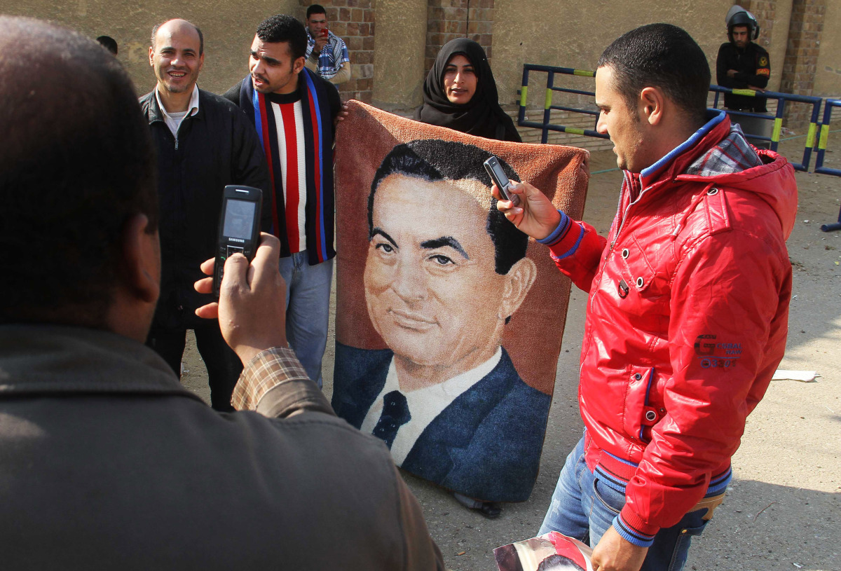 Egyptian supporters of Hosni Mubarak stand in front of a courtroom in Cairo, Egypt, Tuesday, Jan. 3, 2012. The chief prosecut