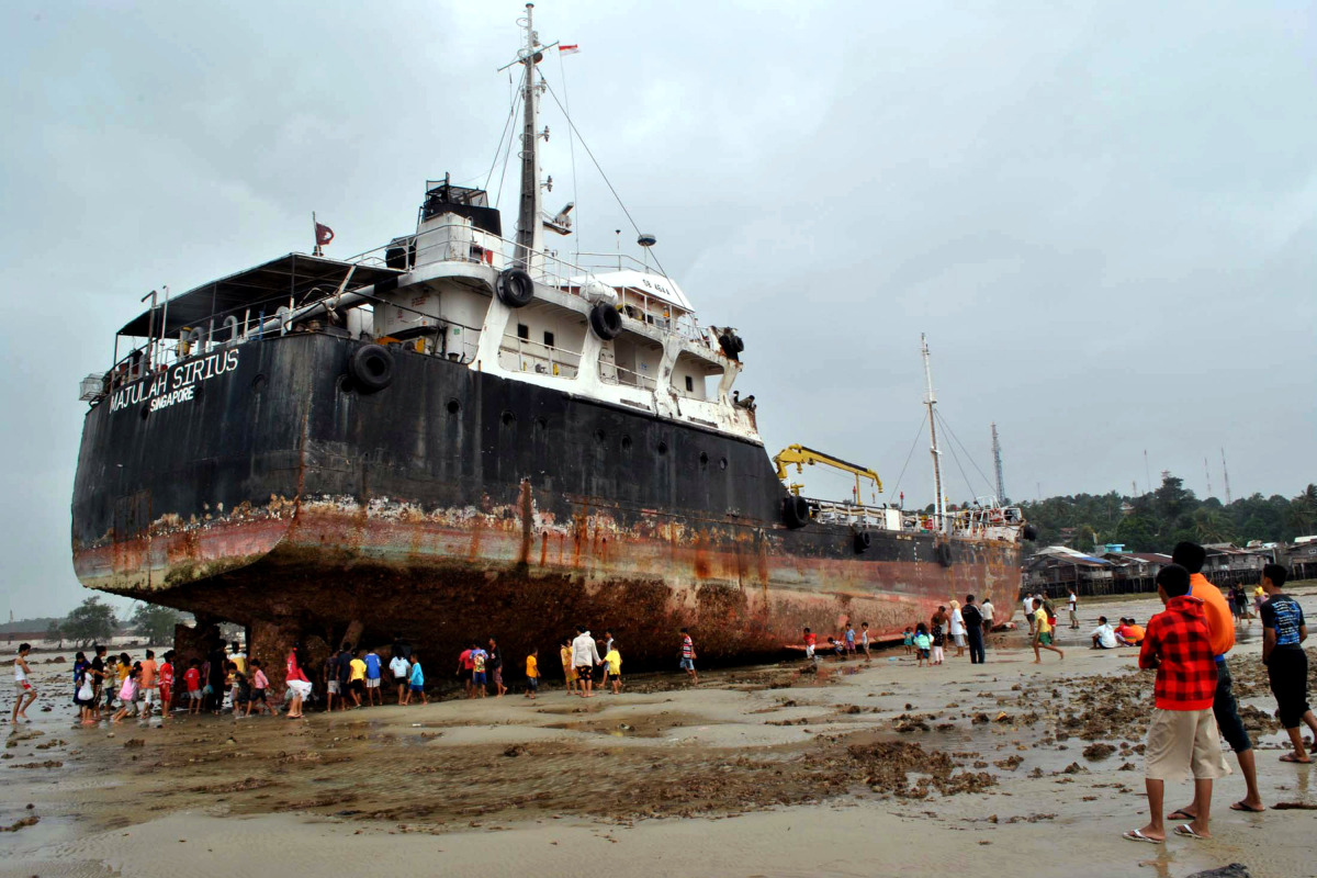 Children play close to the stranded tanker, MT Majulah Sirius number SB 464 A on  Batumerah beach on Dec. 28, 2011 in Batam,