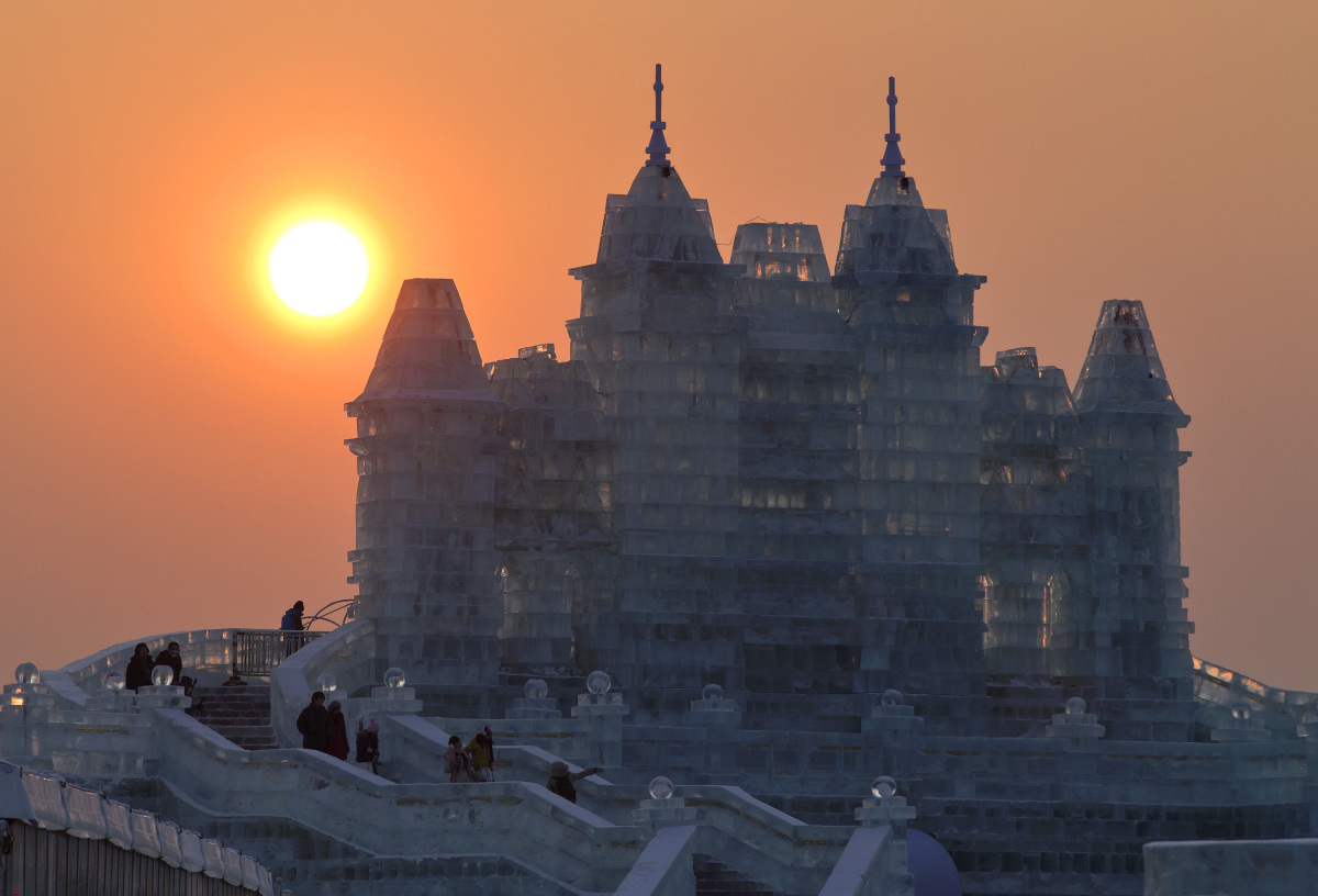 Sunset is seen near a castle made from blocks of ice before the opening ceremony of the Harbin International Ice and Snow fes