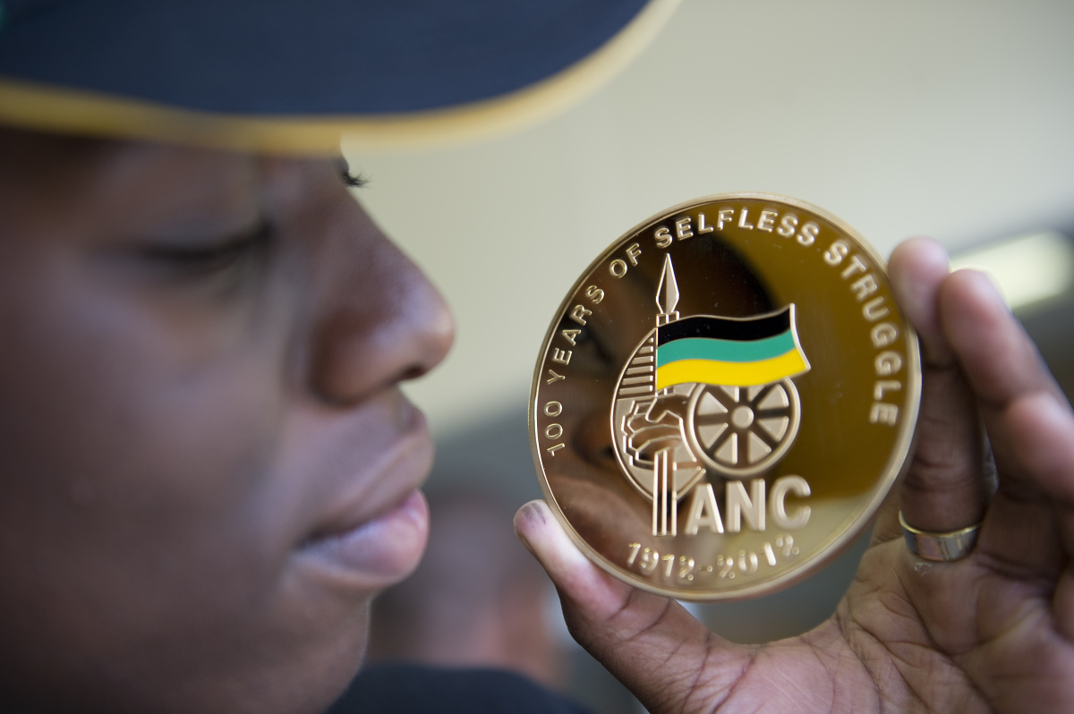 A woman holds up a souvenir medal on sale on the streets in Bloemfontein on January 5, 2012 to celebrate the 100th anniversar