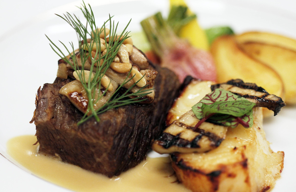 The entree dish, marinated pacific sea and braised prime short rib of beef, roasted fingerling potatoes, candy striped beets,