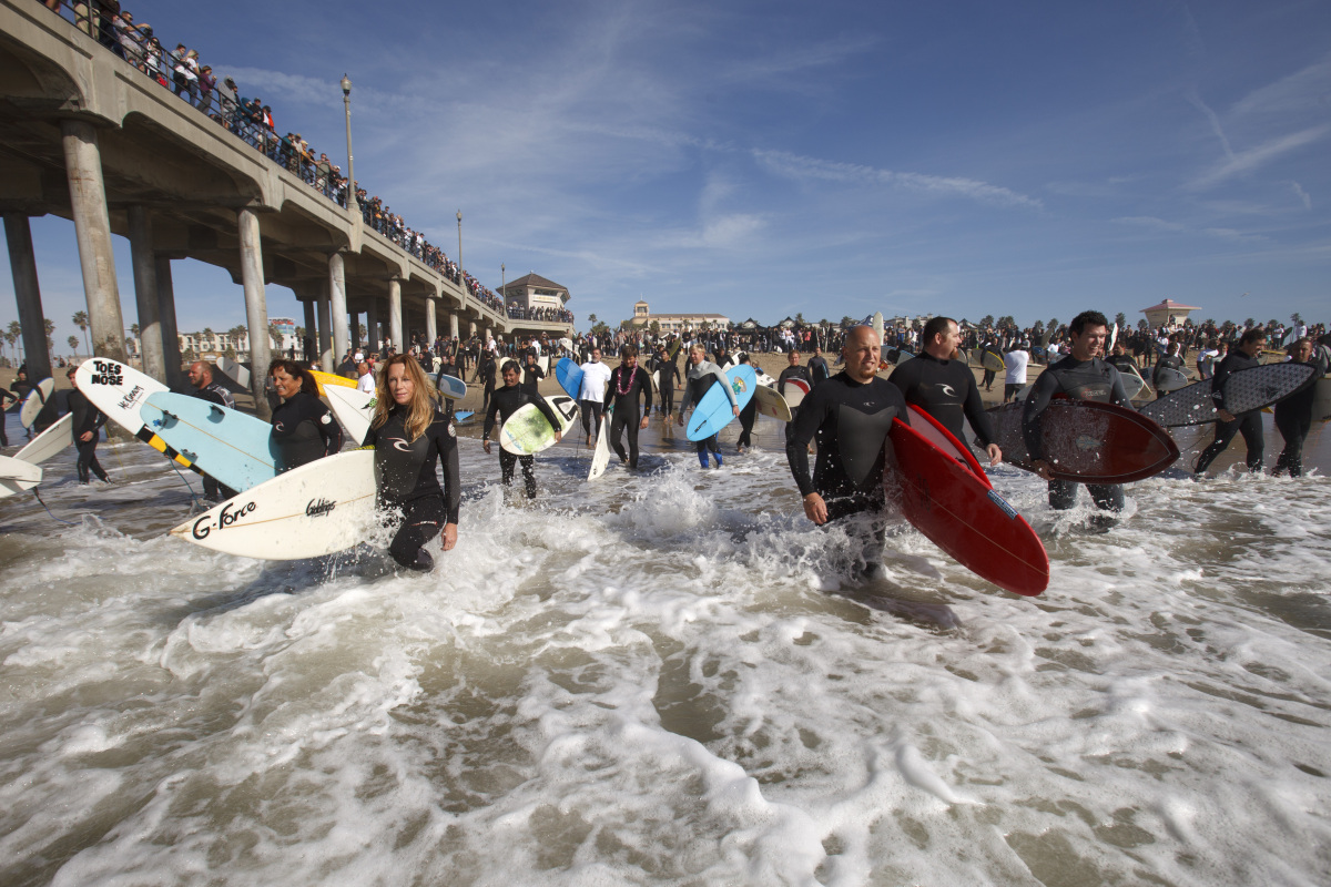 Hundreds of surfers enter the water on their way to form a circle in honor of surf forecaster Sean Collins Sunday, Jan. 8, 20