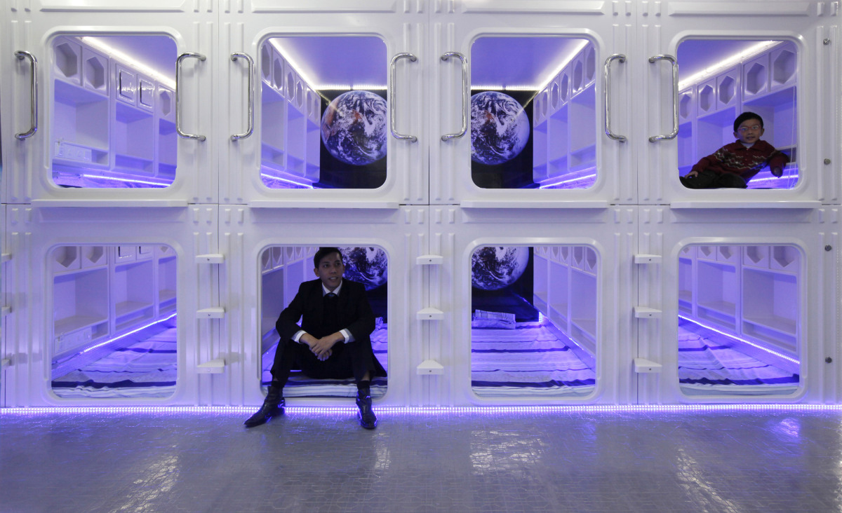 """""""Capsule bed"""" manufacturer Eric Wong, left, and his son Osbert pose inside a modified capsule-like bedroom imported from Japa"""