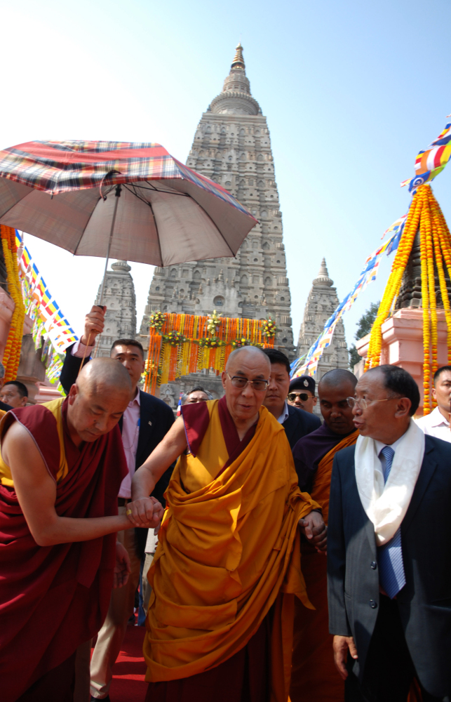 Tibetan Spritual Leader The Dalai Lama (C) walks with officials after offering prayers at The Mahabodhi Temple in Bodhgaya on
