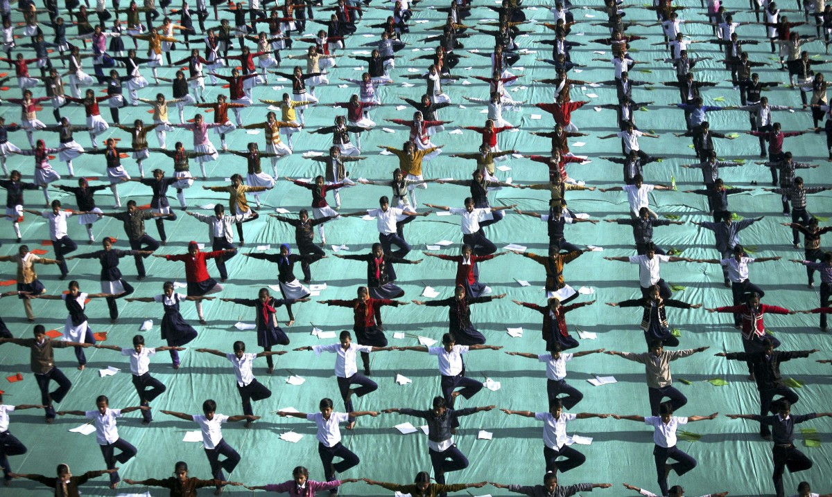 In this Monday, Jan. 9, 2012 photo, Indian schoolchildren perform yoga during a rehearsal for the inaugural ceremony of the I