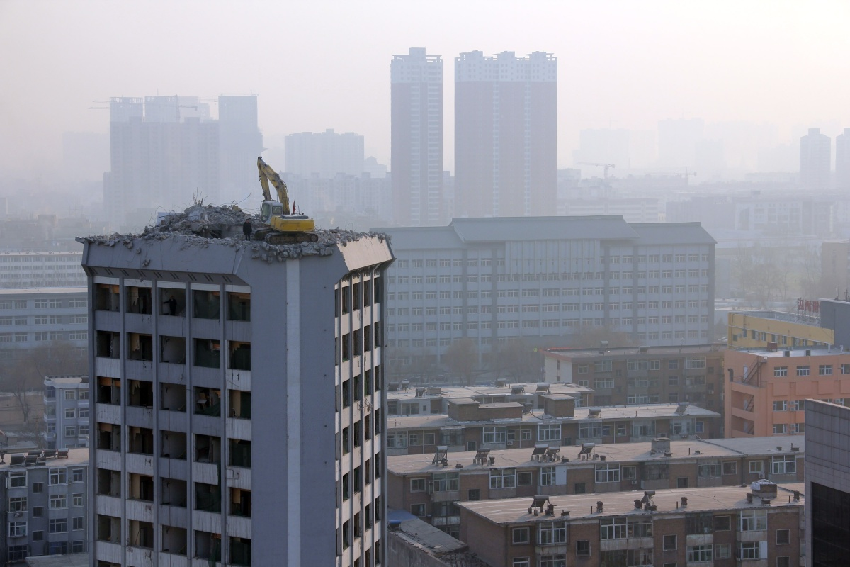 An excavator operates on the rootop of the Shanxi Science and Technology Hotel in Taiyuan, Shanxi Province, China on January