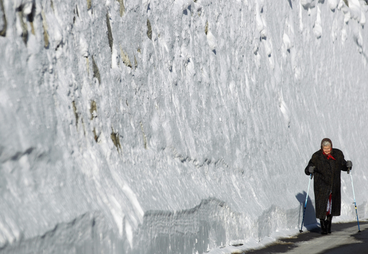 A resident woman walks the mountain road alongside a snow covered wall on Jan. 11, 2012 near Ischgl, Austria. In the last wee