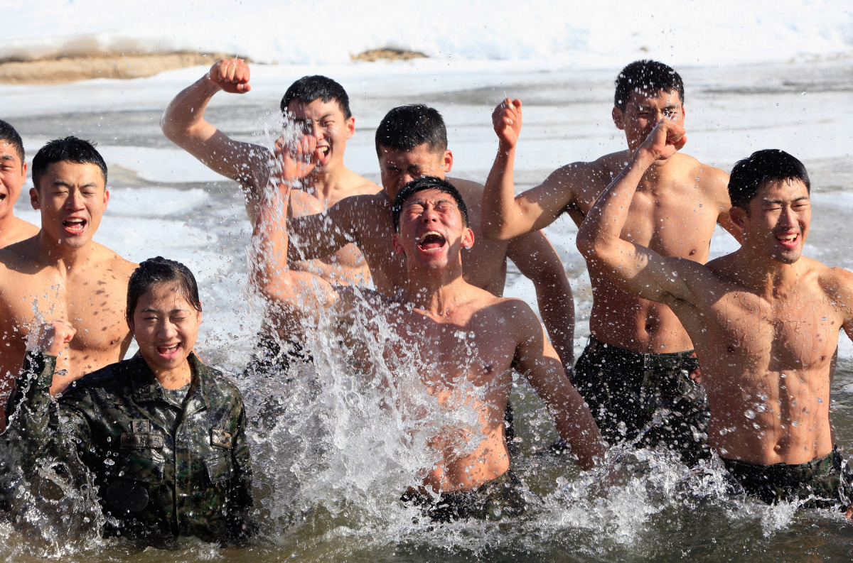 South Korean special warfare command soldiers fool around in a mountain stream in winter mountain training exercises on Janua